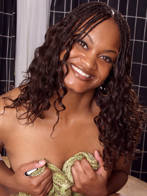 black girl Tyra, topless, clutching her green dress to her breasts.